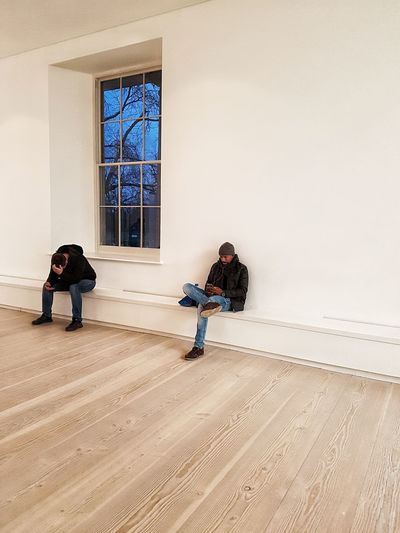 Two Men Indoors  White Background Black Man Black Man And A Cell Phone Cellphone Mobile Phone Technology Communication Using A Phone Using A Phone At A Museum Listening To Music Listening To Music On The Phone Waiting Killing Time Bored Relaxed Desperate Resting