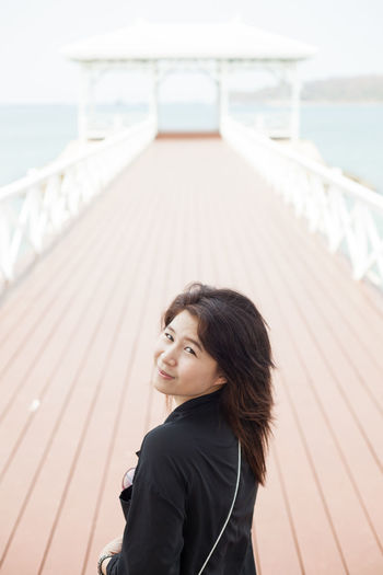 Portrait of young woman standing on pier