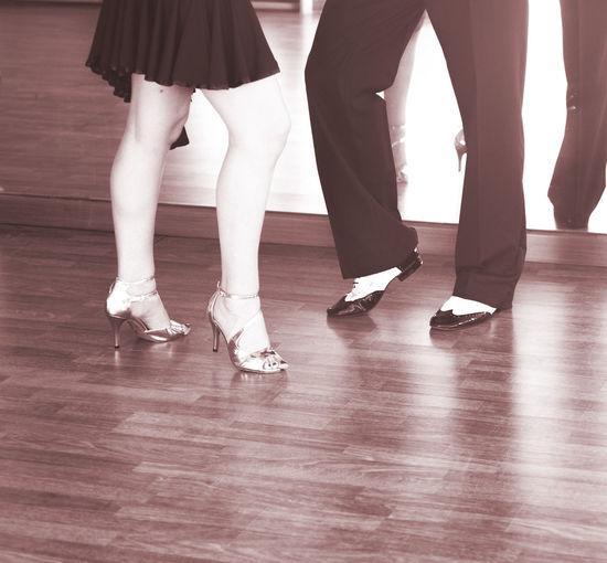 Low section of people dancing on hardwood floor at studio