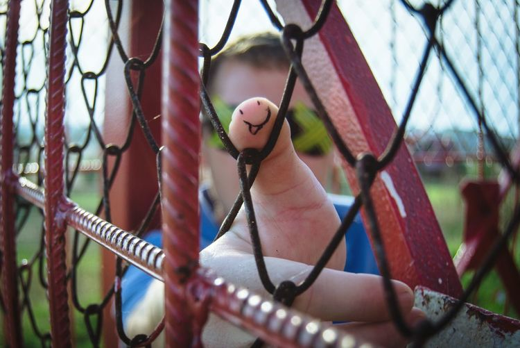 Cropped hand of man on chainlink fence