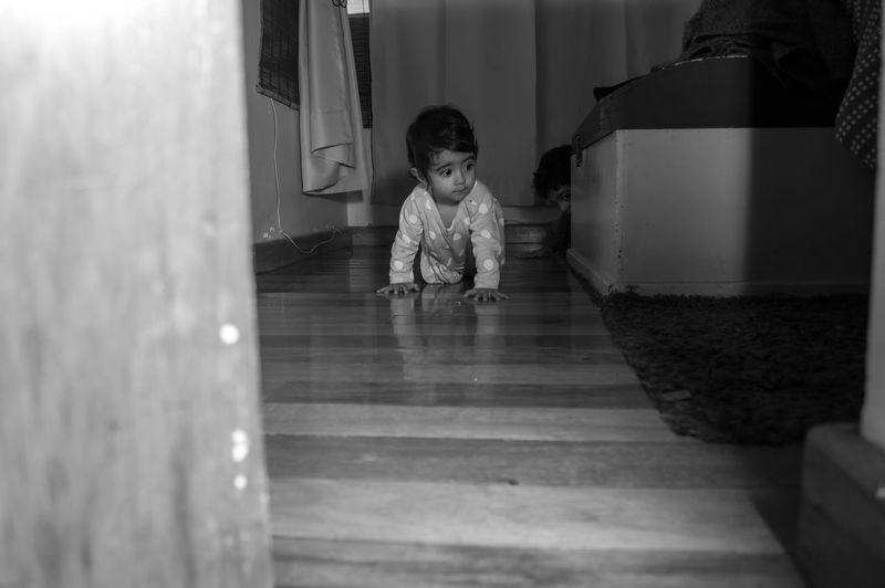 Full length of cute girl crawling on wooden floor at home