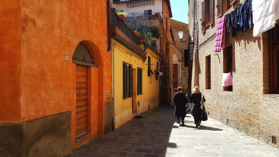 Building Exterior Built Structure Building City Real People Street Day Sunlight Wall - Building Feature Walking Outdoors People Hand In Hand Holding Hands And Walking Yellow Ochre Terracotta Orange Color Siena, Italy Italian Street Mum And Daughter Washing Drying Laundry Hanging Laundry