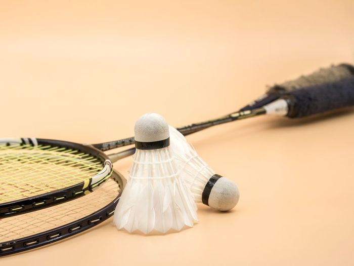 Close-up of shuttlecocks and rackets on beige background