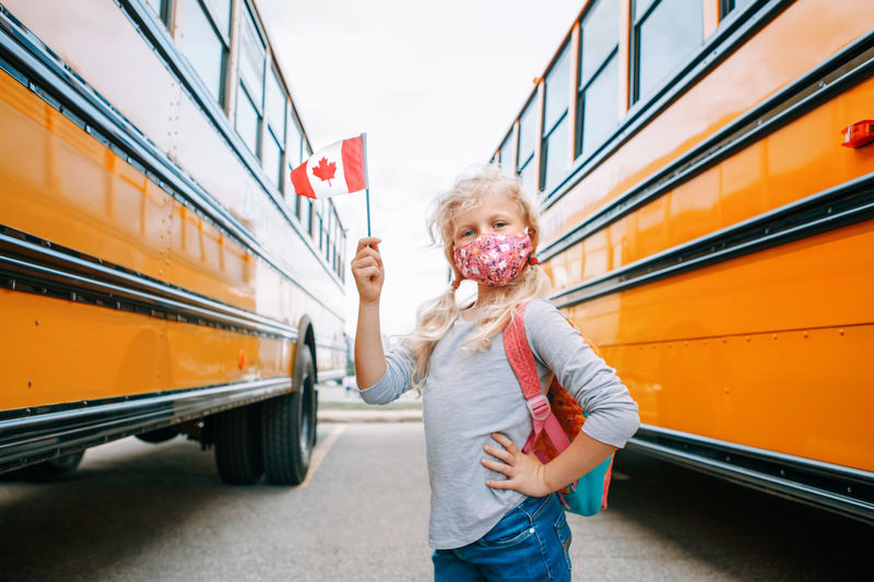 Girl student with face mask holding canadian flag. student kid in new normal during coronavirus.