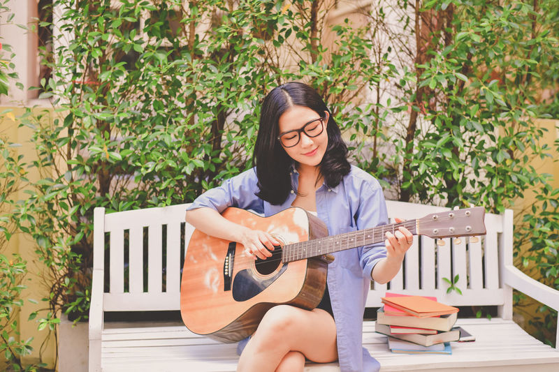Woman playing guitar while sitting on bench at park