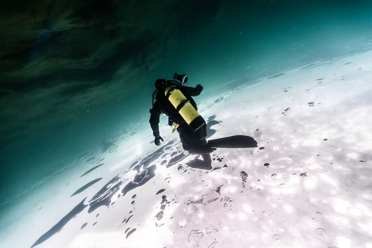 Rear View Of Scuba Diver Under Water