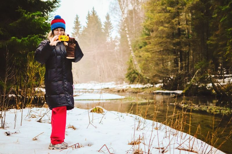 Stand and stare. Capture every idle moment while walking on snow. Young Woman Woman Adult Snow Snowy Forest Female Stream River Woods Winter Winter Clothes Estonia Nelijärve Woolly Hat Gloves Mobile Phone Phone Smart Phone Taking Photos Trees Jacket Nature Outdoors Winter Wear