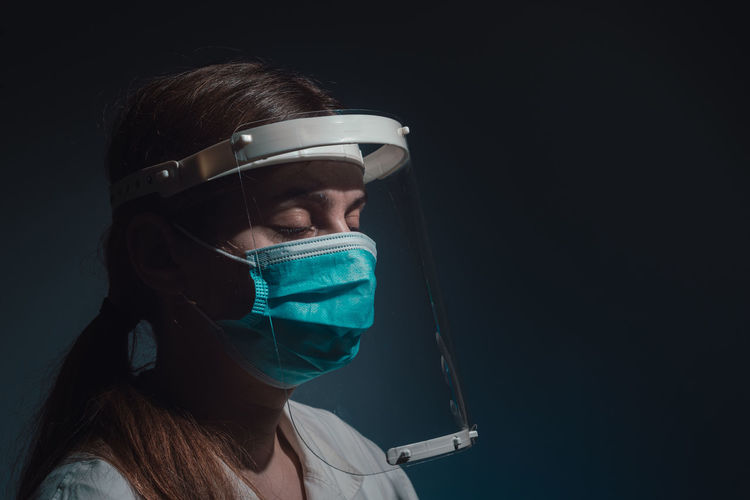 Female doctor with mask and face shield closed eyes