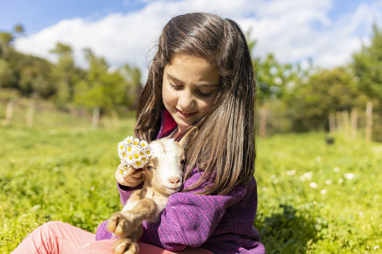 Close-up of smiling girl playing with kid goat on grassy land