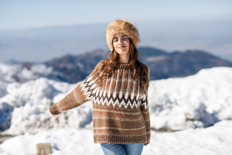 Smiling young woman standing outdoors during winter