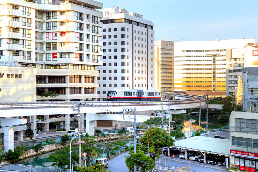 The Yui Monorail snaking through Naha City Architecture Building Building Exterior Built Structure Car City City Life City Street Day High Angle View Land Vehicle Mode Of Transportation Monorail  Motor Vehicle Nature No People Outdoors Plant Public Transportation Residential District Road Street Transportation