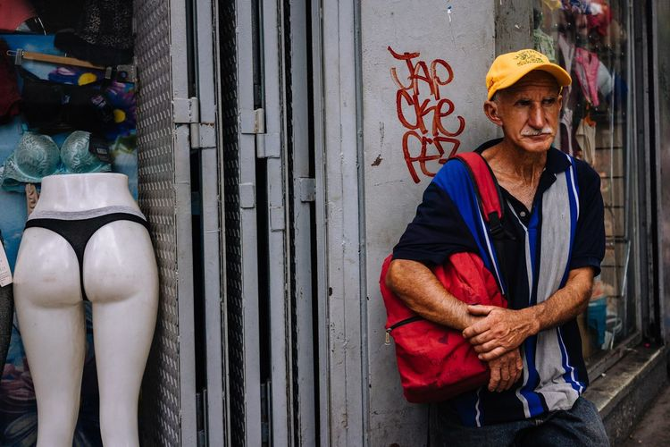 """Butt"" never alone. One Person Adult Front View Real People Portrait Men Looking At Camera Standing Clothing Three Quarter Length Casual Clothing Arms Crossed Mature Adult Day Lifestyles Sitting Males  City Architecture Mature Men Streetphotography Street Photography Streetphoto EyeEm Best Shots EyeEm Selects The Street Photographer - 2019 EyeEm Awards"