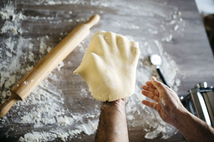Cropped hands of man holding dough in kitchen