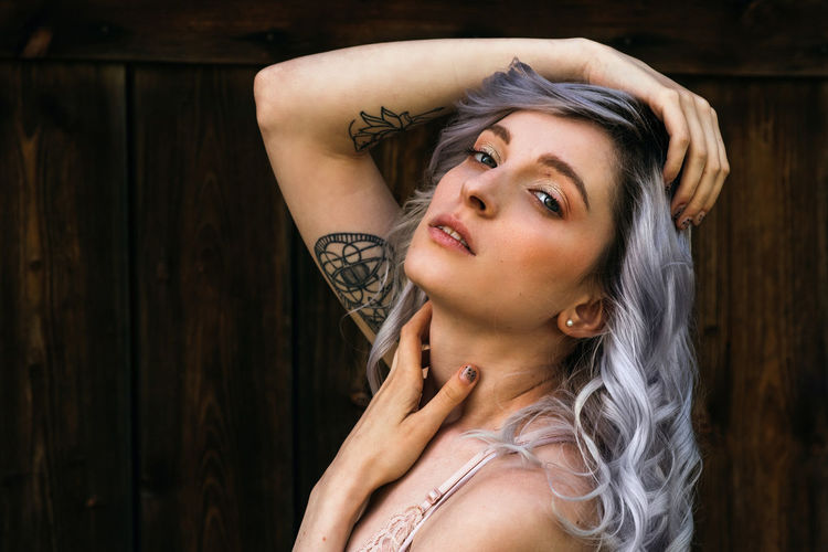 Alternative Arms Raised Beautiful Woman Beauty Front View Hair Hairstyle Headshot Human Arm Lifestyles Looking At Camera Portrait Purple Hair Real People Tattoo Women Wood - Material Young Adult Young Women