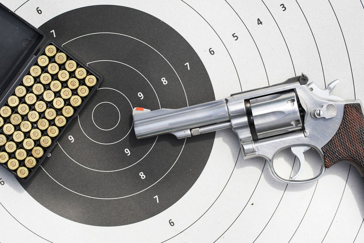 Close-Up Of Gun And Bullets On Sports Target