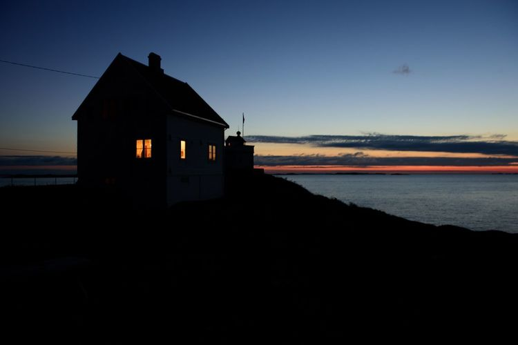 Silhouette house by sea against sky at sunset