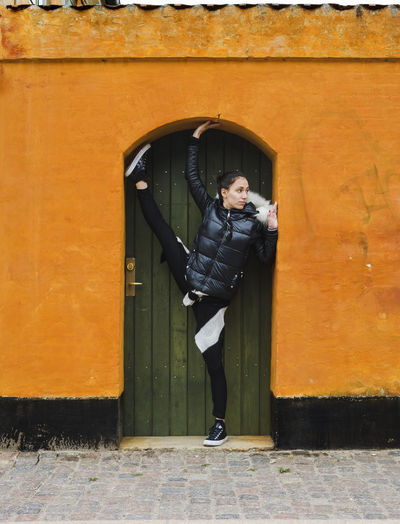 Full length of woman stretching legs against door
