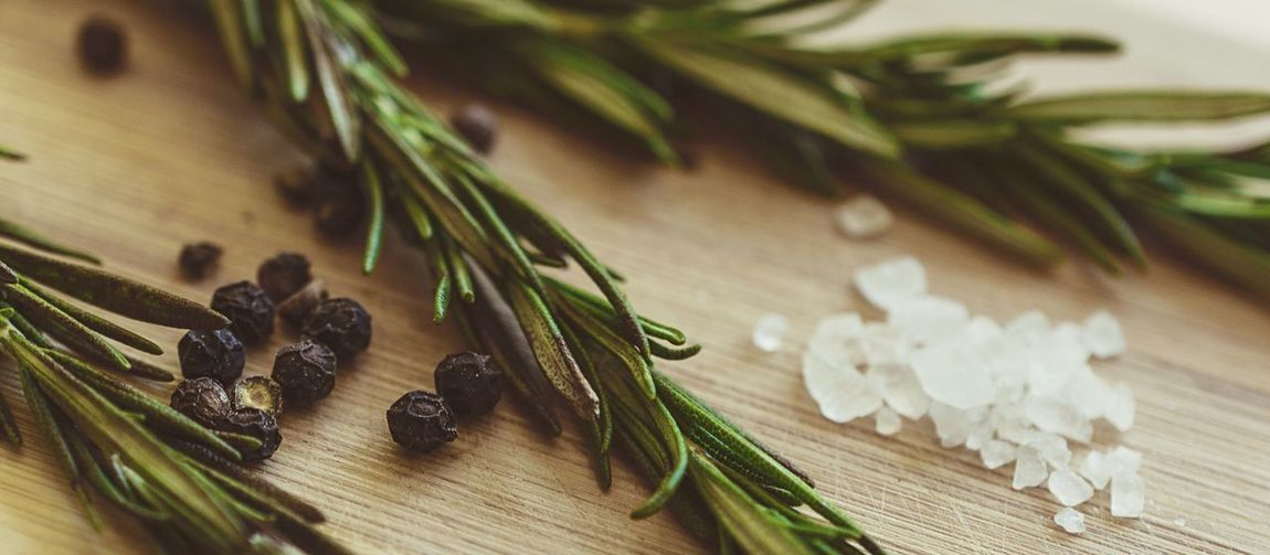 Close-up of rosemary and black peppercorns with salt on table