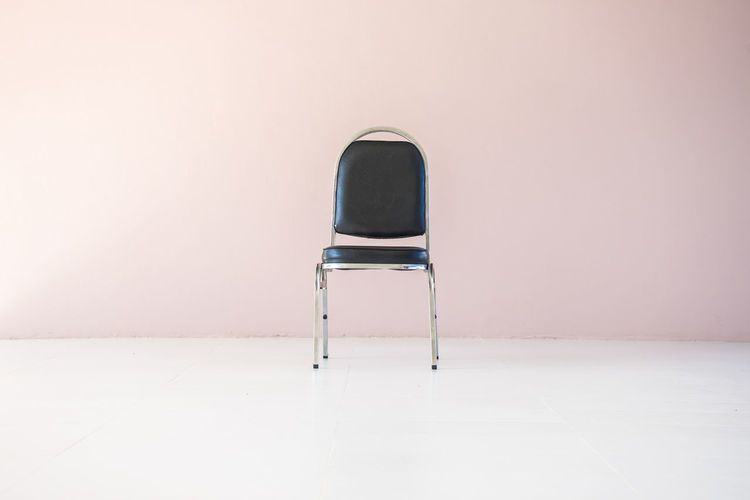 Empty chair on table against wall