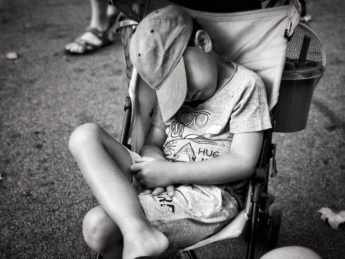 Boy sleeping on chair at field