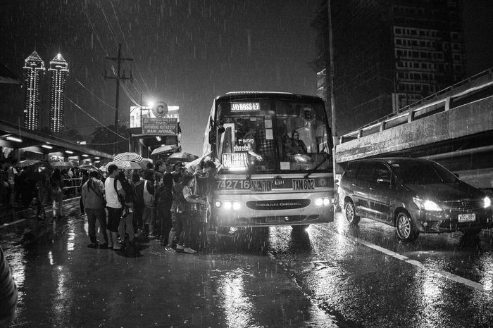 Commuters eager to get home after a long day of work got caught on heavy downpour along EDSA in Ortigas, Quezon City as they fight their way on an available bus. September 2015. Documentary Photography Everybodystreet EyeEm Best Shots EyeEm Phillipines EyeEmBestPics Street Photography The Human Condition The Photojournalist - 2016 EyeEm Awards Untold Stories MyCommute