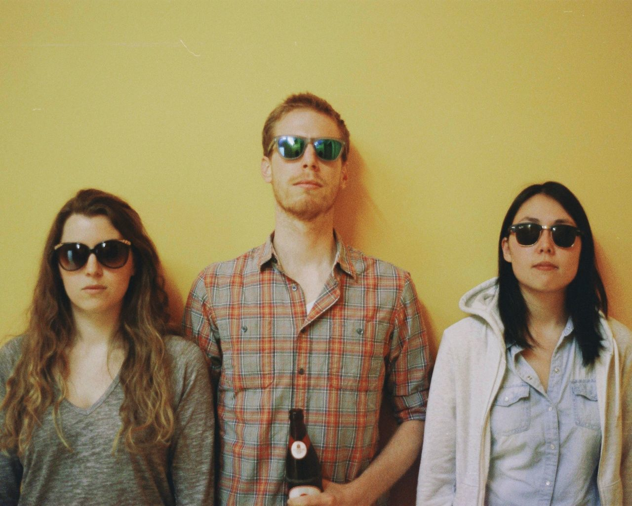 Portrait of three young adults over yellow background