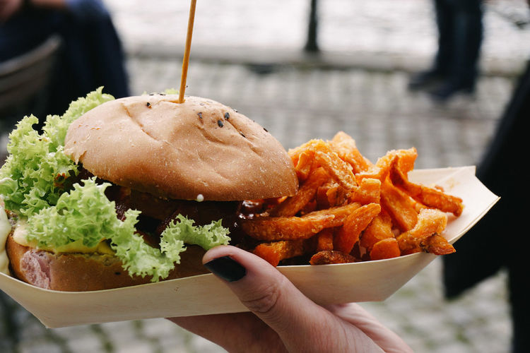 Close-up of hand holding burger and french fries in paper plate