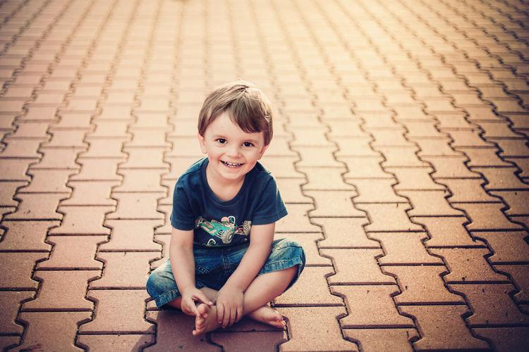Portrait of smiling boy sitting on footpath