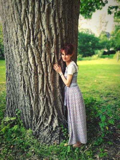 Full length of woman with tree trunk against plants