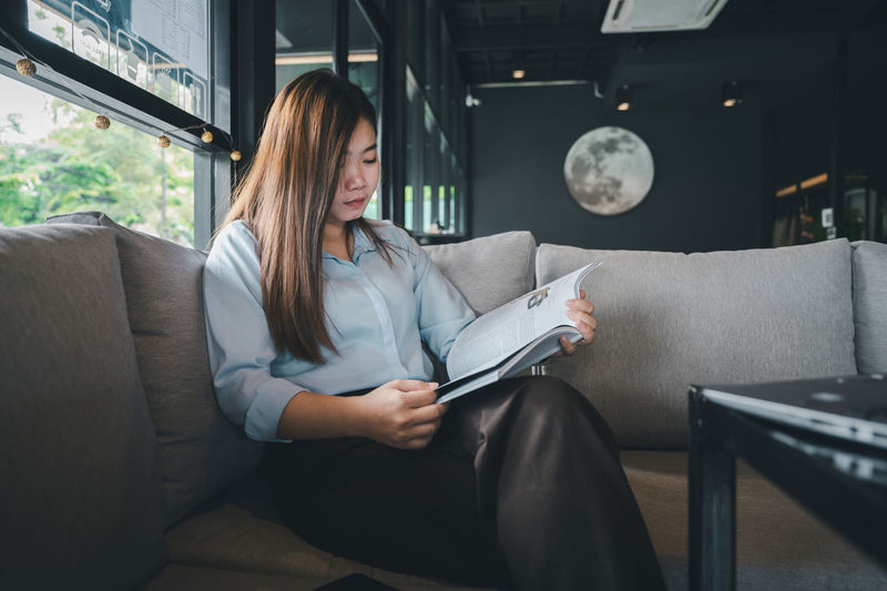 Midsection of woman holding paper while sitting on sofa