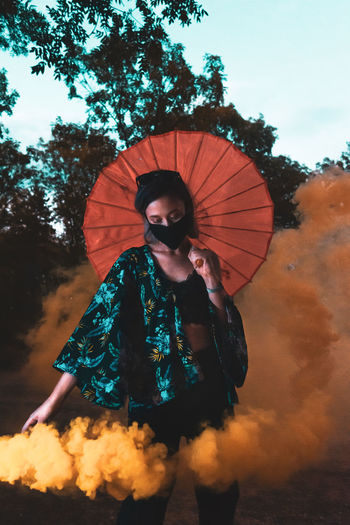 Woman holding umbrella against sky