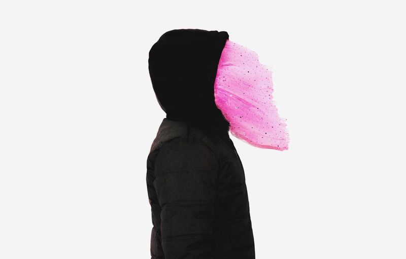 Side view of woman wearing pink textile with hooded shirt against white background