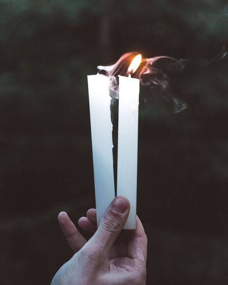Close-Up Of Hand Holding Candles