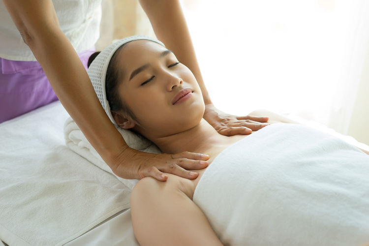 Cropped Hands Of Massage Therapist Massaging Young Woman Shoulders In Spa