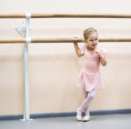 Cute Ballet Dancer Standing Against Wall