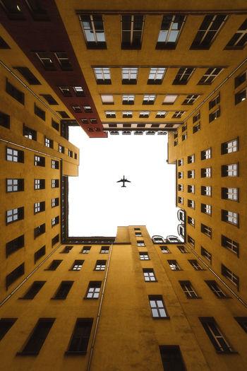 Directly Below Shot Of Airplane Flying In Sky Over Buildings