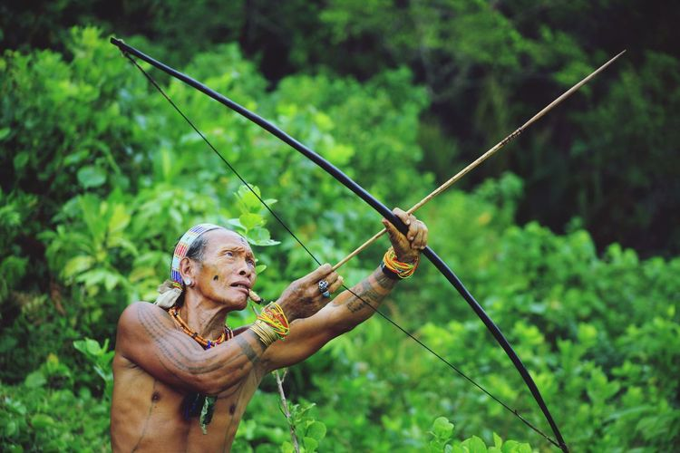 Shirtless man holding bow and arrow while standing against trees