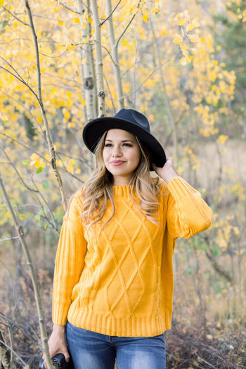 Portrait of smiling woman standing against yellow during autumn