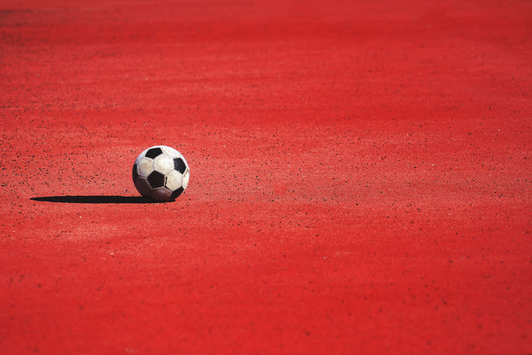 Soccer ball on red land during sunny day