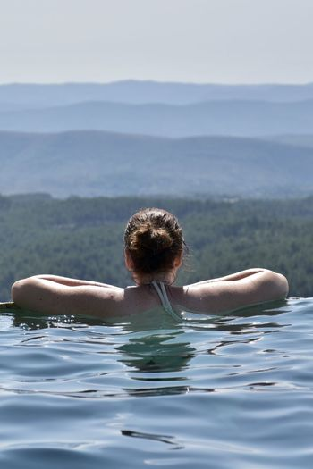 Rear view of a woman in an infinity pool looking over the valley and the landscape