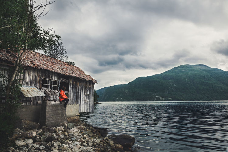Woman In Old Building By Lake Against Cloudy Sky