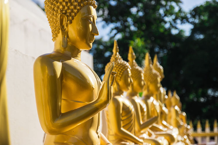 Golden Buddha Statues In Row During Sunny Day