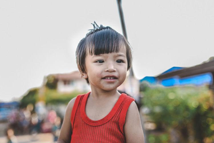 Smiling girl standing against sky