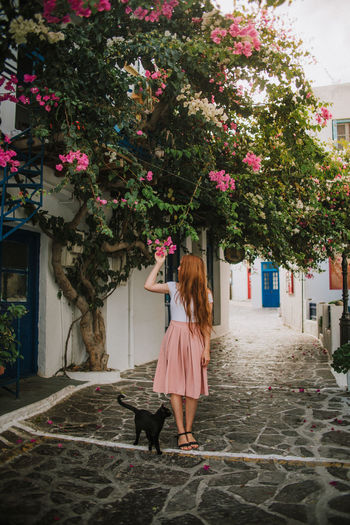 Girl standing by flowering tree