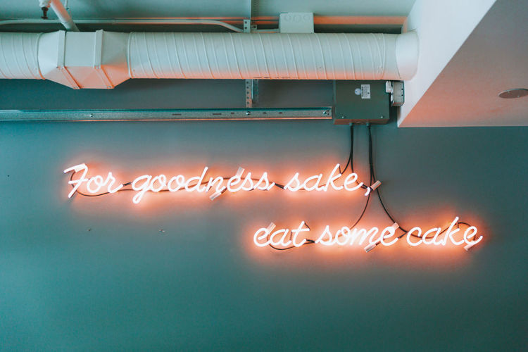 A sign that says to eat cake. Illuminated Text Glowing Indoors  Sign Electricity  Cake