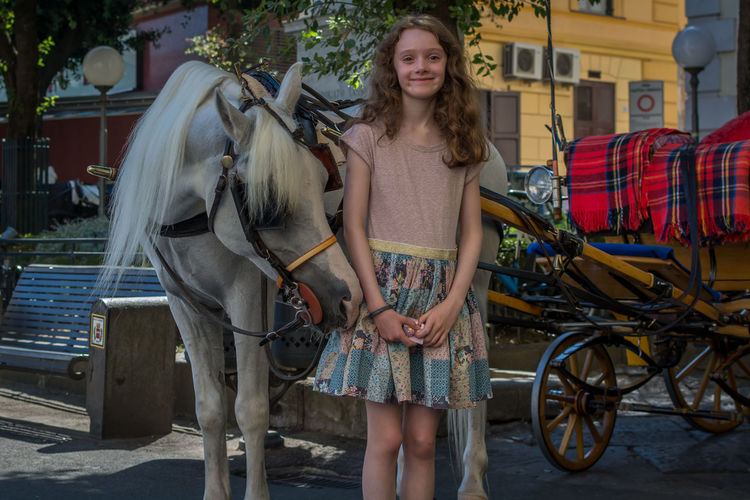 Portrait of smiling young woman standing by horse cart