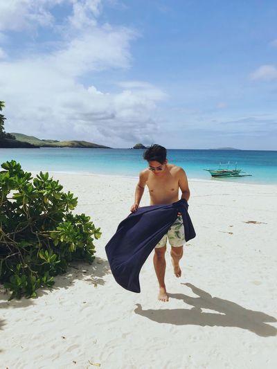Full length of shirtless man walking at beach against sky