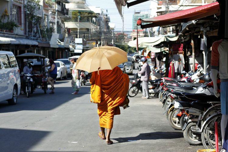 Rear View Of Monk Walking On Road