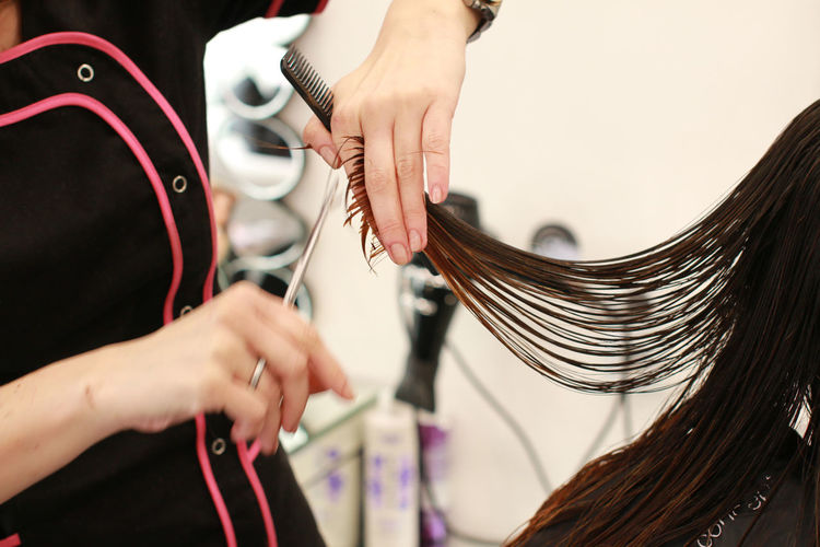 Midsection of hairdresser cutting woman hair