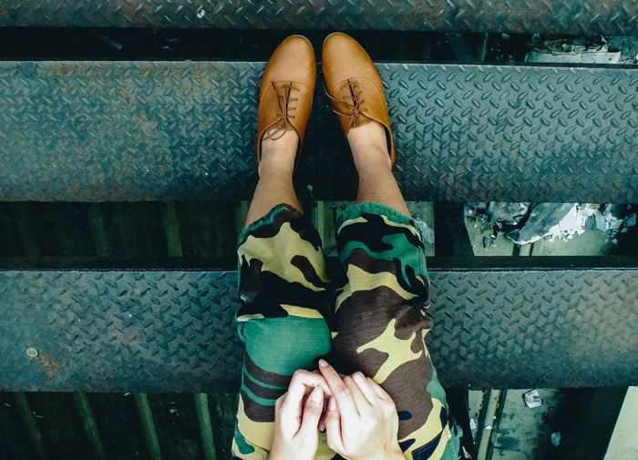 Upside Down Image Of Woman Wearing Shoes While Sitting On Steps